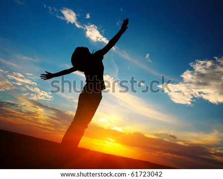 Young woman with raised hands standing on land over sunset light