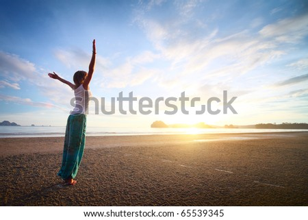 Young woman with raised hands standing on sand and looking to a sky