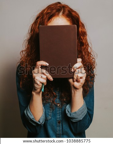 Young woman with red curly hair covered her face with a book