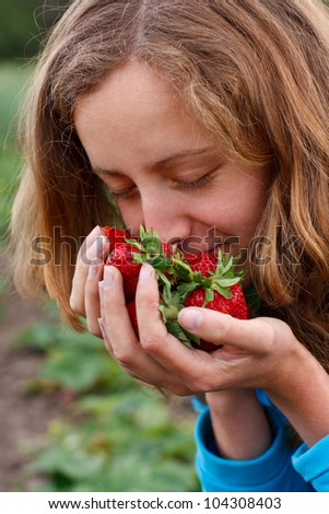 Young woman with red fresh strawberries in hands. Enjoying the aroma of ripe strawberries