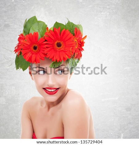 young  woman with red gerbera flowers on her head  looking to her side, on a gray background