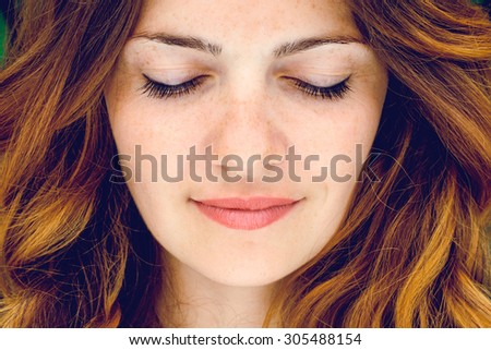 Shutterstock Young woman with red hair and closed eyes in a park