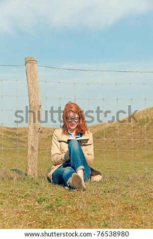 Young woman with red hair and glasses sitting in nature reading book.