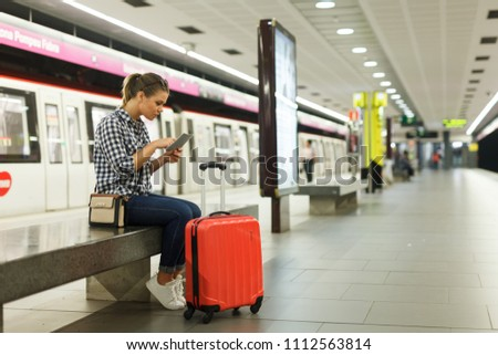 Young woman with red suitcase waiting for train at metro station sitting on stone bench