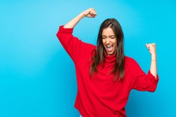 Young woman with red sweater over isolated blue background celebrating a victory