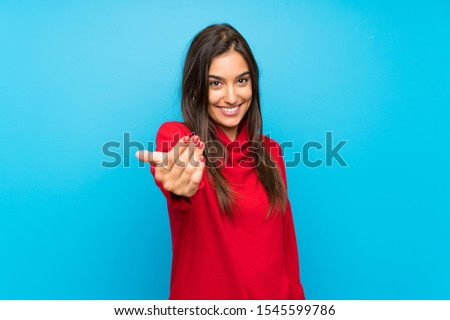 Young woman with red sweater over isolated blue background inviting to come ストックフォト ©