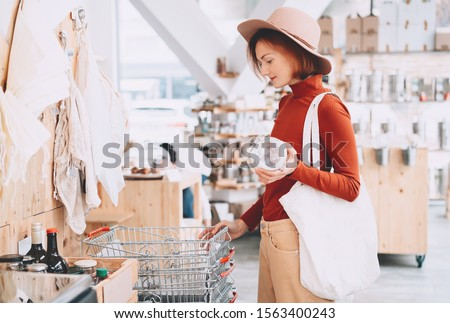 Young woman with reusable cotton bag and empty jar doing shopping in plastic free store. Minimalist vegan style girl buying groceries without plastic packaging in zero waste shop. Low waste lifestyle.
