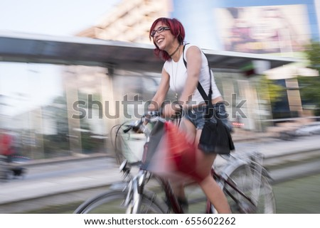 Young woman with ride bike in the city at high speed