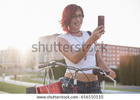 Young woman with ride bike in the city. Posing with sunset back light smiling in city park.