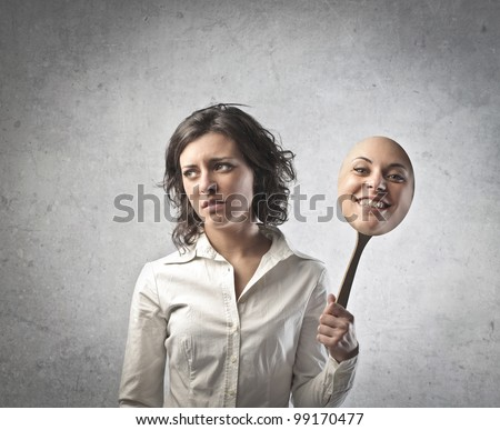 Young woman with sad expression holding a mask expressing cheerfulness