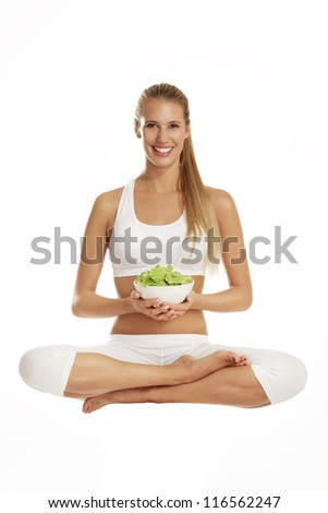 young woman with salad after fitness on white
