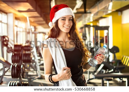 Stock Photo Young woman with Santa hat, bottle of water and towel in the gym. New Year. Christmas, holidays, fitness, and gym concept.