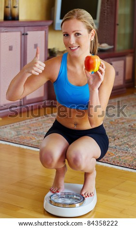 Young woman with scales and apple. Successful Diet