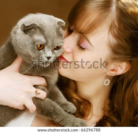 Young woman with scottish-fold cat.On brown background.