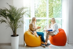 Young woman with senior female psychologist or mental coach sitting on the comfortable chairs during the psychological counseling in the office
