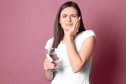 Young woman with sensitive teeth and glass of cold water on color background