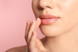 Young woman with sexy lips on color background, closeup