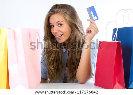 young woman with shopping bags and credit card on white background