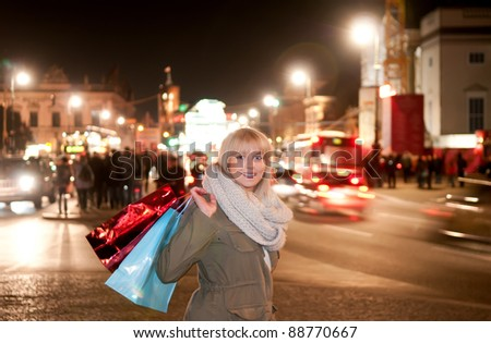 young woman with shopping bags in the city at night