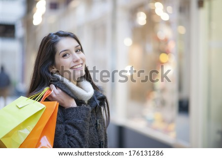 young woman with shopping bags, shops lights in background