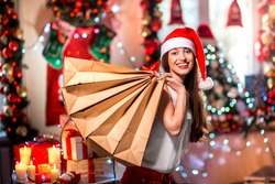 Young woman with shopping bags with Christmas decorations, candles, gifts and lights on bachground. Christmas sale