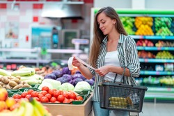 Young woman with shopping basket checks and examines a sales receipt after purchasing food in a grocery store. Customer buying products at supermarket