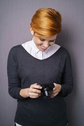 Young woman with short red hair in dark sweater looking down at photo camera display and smiling, standing indoors