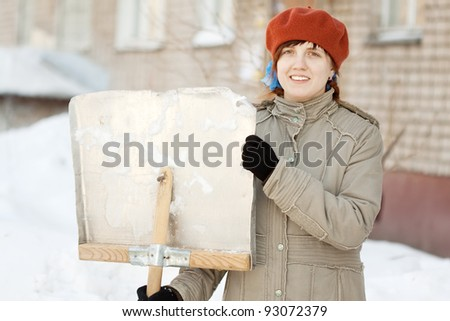 young woman with shovel in winter outdoor