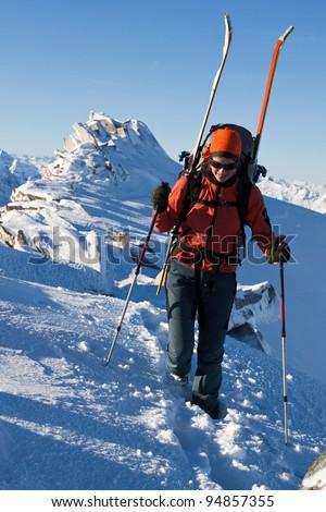 Young woman with ski on a mountain ridge