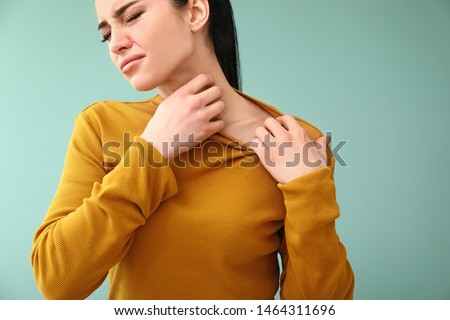 Young woman with skin allergy on color background