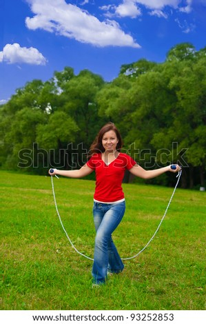Young woman with skipping rope on the lawn