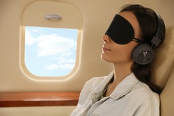 Young woman with sleep mask resting while listening to music in airplane during flight