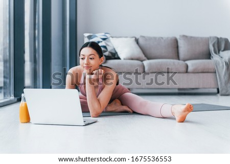 Young woman with slim body shape in sportswear sits on mat with orange juice and laptop indoors at home.