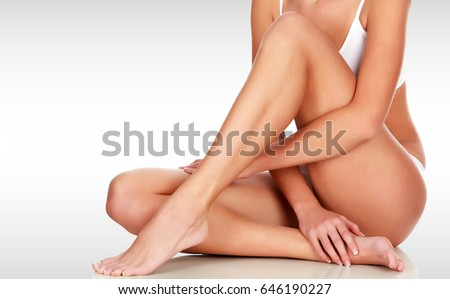Young woman with slim body, smooth and soft skin against a grey background with copyspace