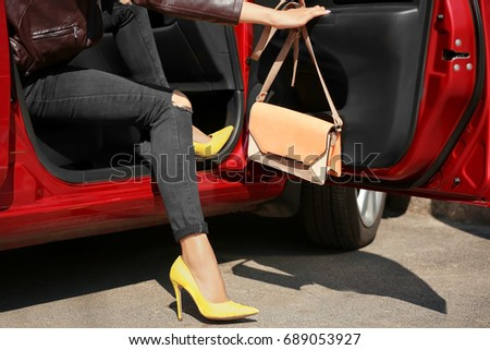 adb23ff4065 Young woman with slim legs in high heels getting out of car  689053927