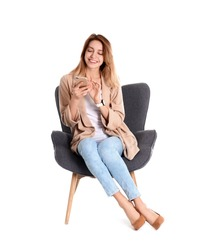 Young woman with smartphone sitting in armchair on white background