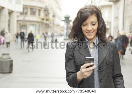 Young Woman with smartphone walking on street, downtown. In background is blurred street