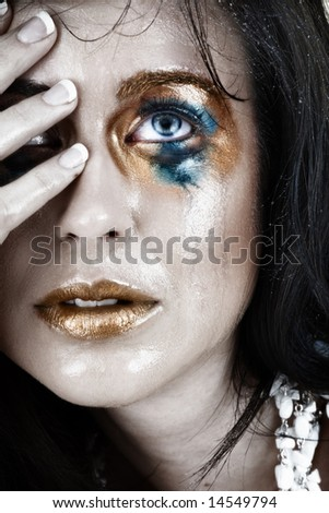 young woman with smudged make-up and face wet from tears with very upset expression