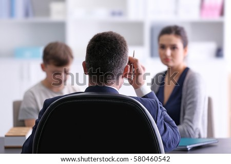 Young woman with son during teacher-parent meeting at school