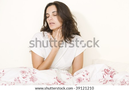 Young woman with sore throat sitting on her bed
