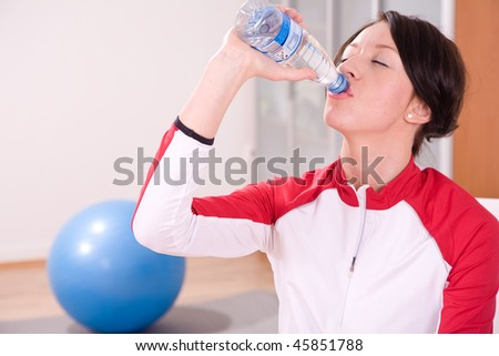 young woman with stability ball sport coach drinking