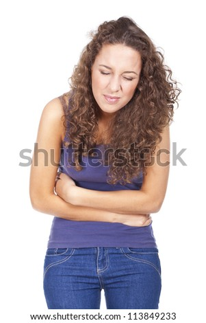 Young woman with stomach pains in studio with white background...