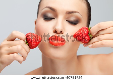 Young woman with strawberry. Portrait of young woman with bare shoulders holding ripe strawberry to lips, white studio background. - stock photo