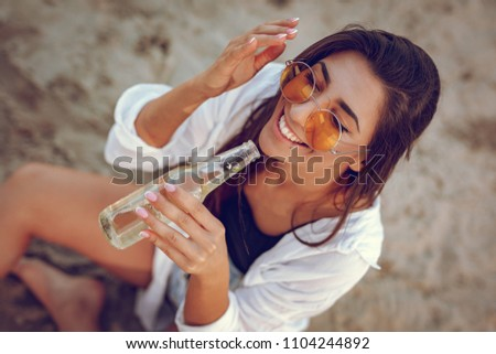 Young woman with sunglasses relaxing at sunset time on the beach. She is sitting by the river and drinking beer. Top view.