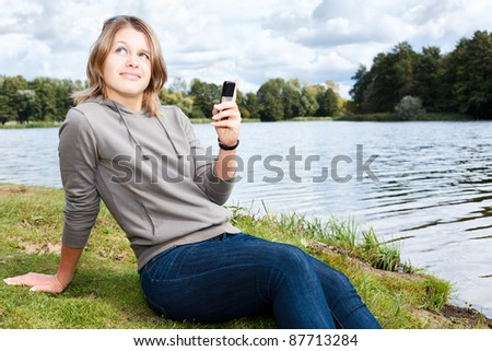 Young woman with sunglasses sitting on the shore of river and reading a message on the cellphone