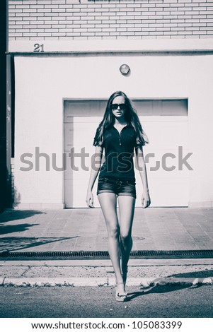 young woman with sunglasses walk down the street, summer day, black and white