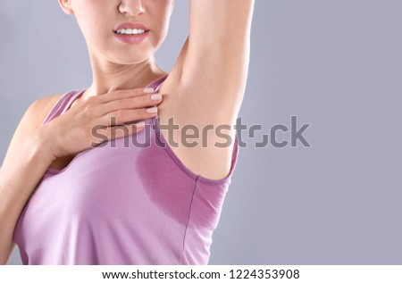 Young woman with sweat stain on her clothes against grey background, space for text. Using deodorant Сток-фото ©