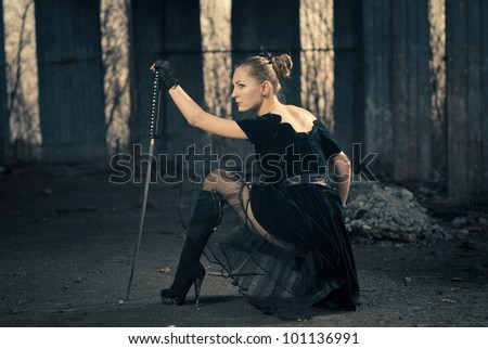 young woman with sword at abandoned place