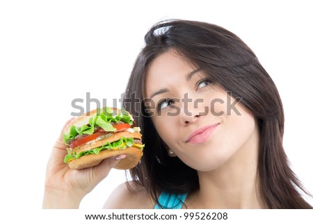 Young woman with tasty fast food unhealthy burger in hand getting ready to eat isolated on a white background. Focus on hand with hamburger.
