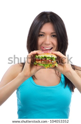 Young woman with tasty fast food unhealthy burger in hand hungry getting ready to eat isolated on a white background